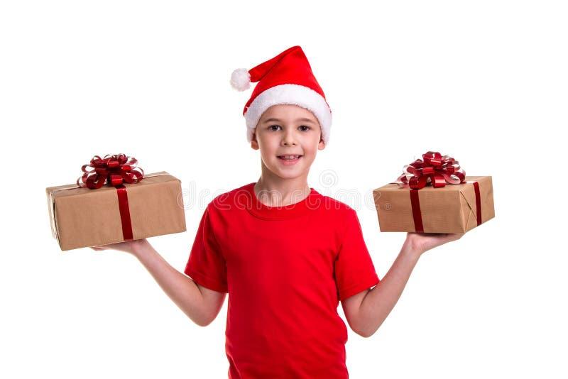Knappe gelukkige jongen, santahoed op zijn hoofd, met twee giftdozen op de handen, die recht aan de camera kijken Concept royalty-vrije stock afbeeldingen