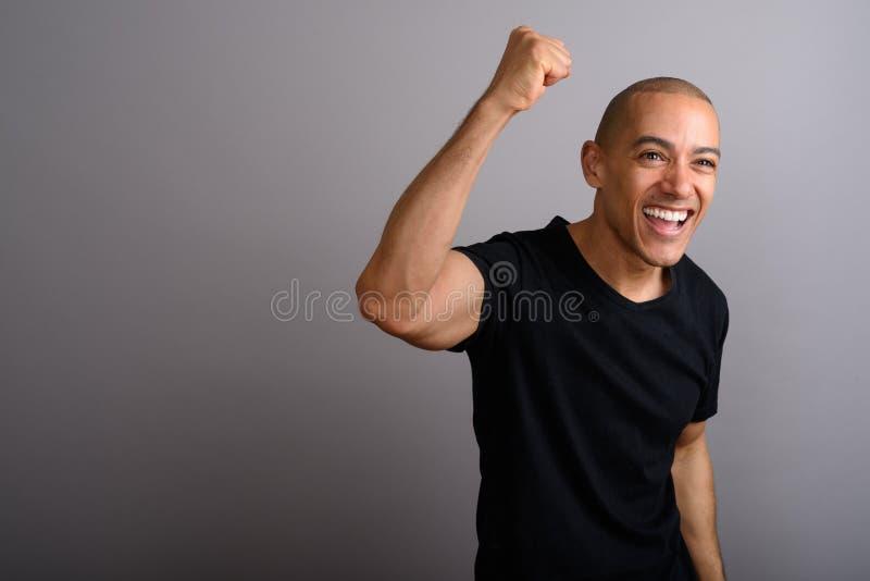 Knappe gelukkige kale mens die met opgeheven wapen glimlachen royalty-vrije stock fotografie
