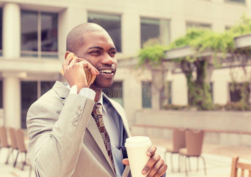 Knappe gelukkige zakenman die op mobiele telefoon het drinken koffie spreken stock afbeeldingen