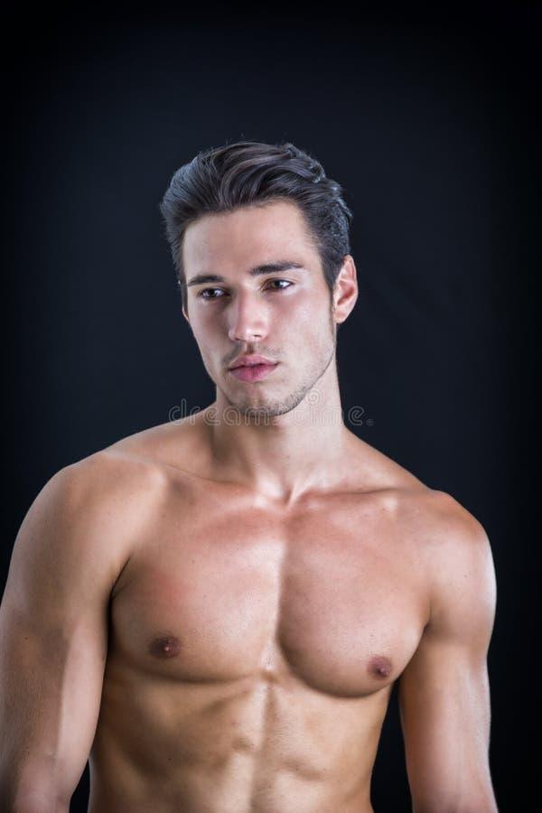 Knappe, geschikte topless jonge die mens op zwarte wordt geïsoleerd royalty-vrije stock afbeelding