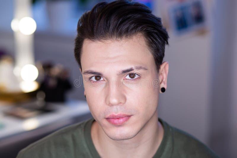 Knappe geschoren donker-haired kerelzitting in heldere studiolichten stock fotografie