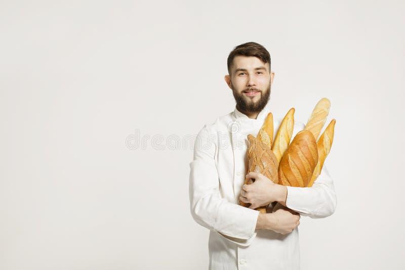 Knappe glimlachende bakker in eenvormige holdingsbaguettes met brood s stock foto