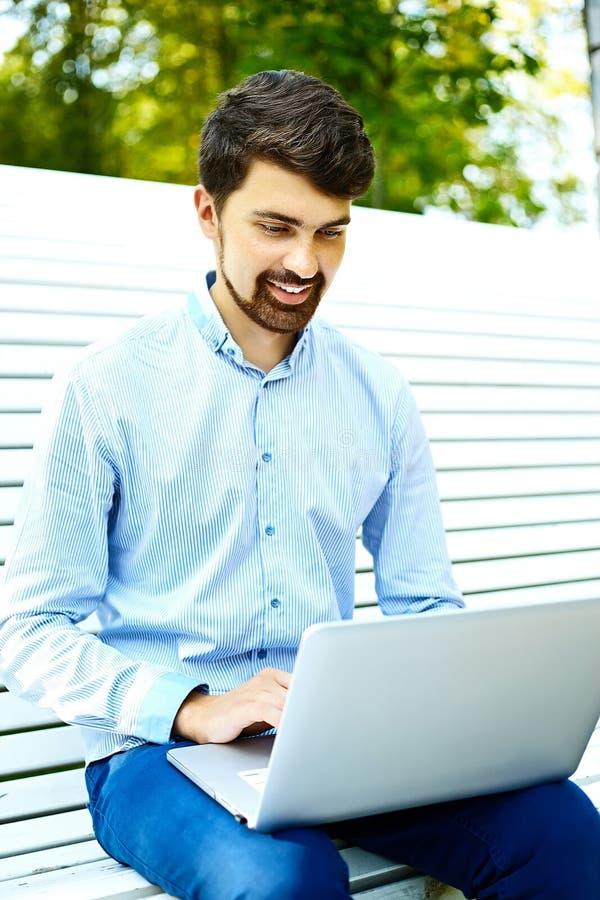 Knappe glimlachende hipster mens in het park stock foto's