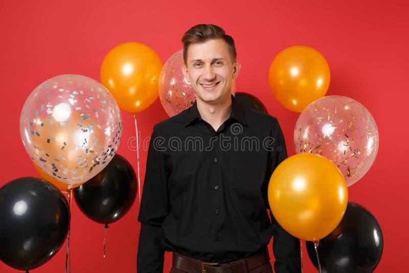 Knappe glimlachende jonge mens in het zwarte klassieke overhemd vieren op heldere rode achtergrondluchtballons St Valentine ` s stock afbeeldingen