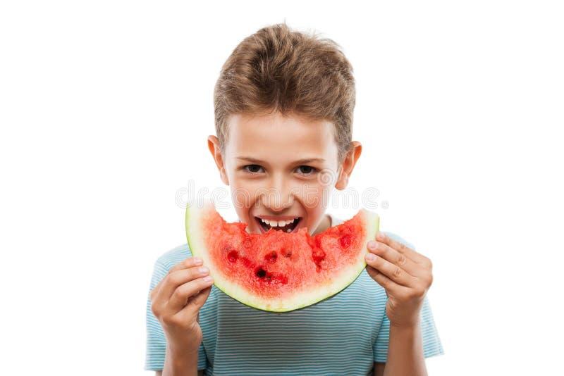 Knappe glimlachende kindjongen die de rode plak van het watermeloenfruit houden stock fotografie