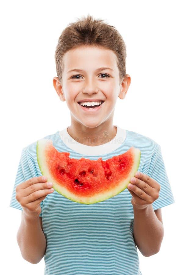 Knappe glimlachende kindjongen die de rode plak van het watermeloenfruit houden stock afbeelding