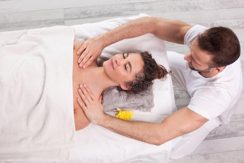 Knappe glimlachende masseur die massage doen stock foto's