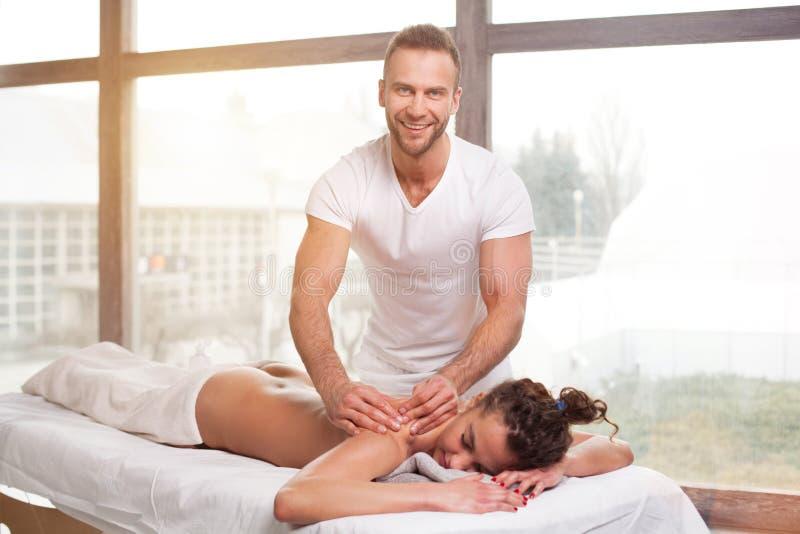 Knappe glimlachende masseur die massage doen royalty-vrije stock afbeeldingen