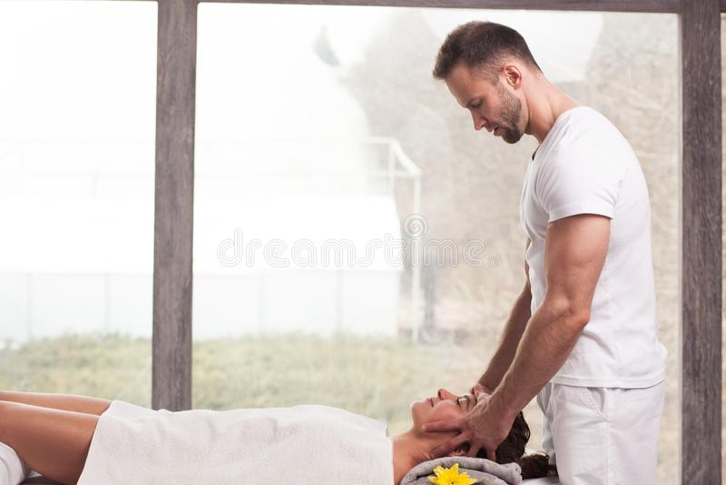 Knappe glimlachende masseur die massage doen stock afbeeldingen