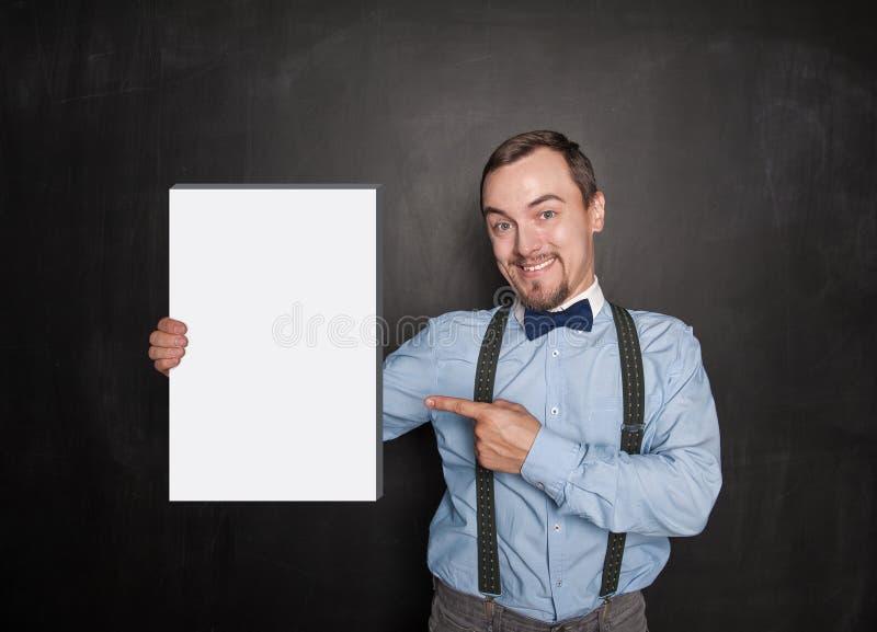 Knappe glimlachende mens die op lege doos in zijn hand op bord tonen royalty-vrije stock foto
