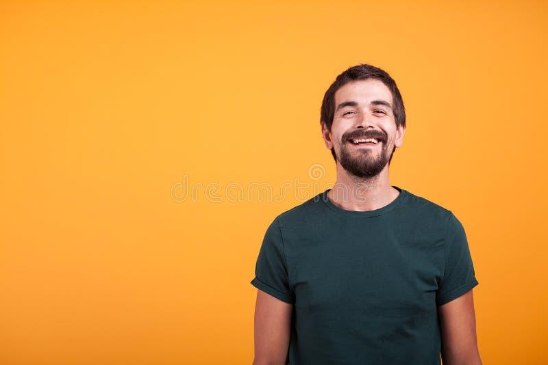 Knappe glimlachende mens met wapens bij zijn rug op oranje achtergrond royalty-vrije stock afbeeldingen