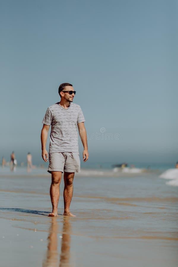 Knappe glimlachende mens in zonnebril die en van dag op het strand lopen genieten stock afbeeldingen
