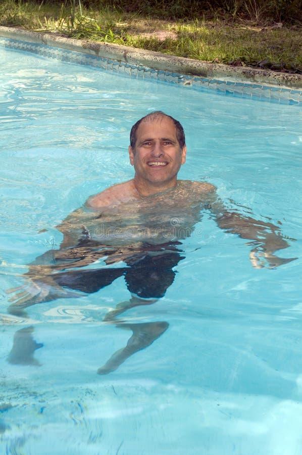 Knappe glimlachende middenleeftijdsmens die in pool zwemt royalty-vrije stock foto's