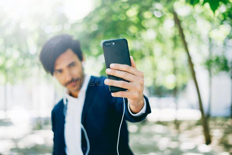 Knappe glimlachende zakenman die smartphone voor het listining van muziek gebruiken terwijl het lopen in stadspark Jonge mens die stock foto