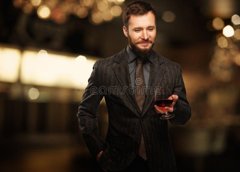 Knappe goed-geklede mens met glas stock afbeelding