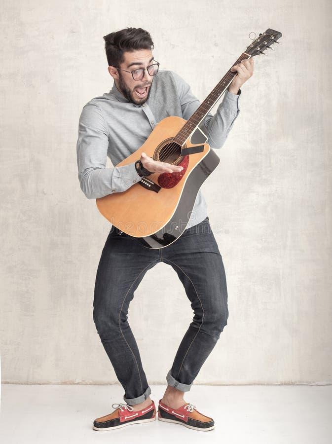 Knappe grappige mens die een akoestische gitaar spelen tegen grungemuur stock afbeelding