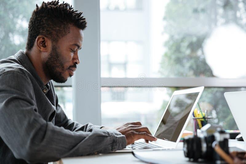 Knappe het denken ernstige jonge mensenzitting in bureau het coworking royalty-vrije stock afbeelding