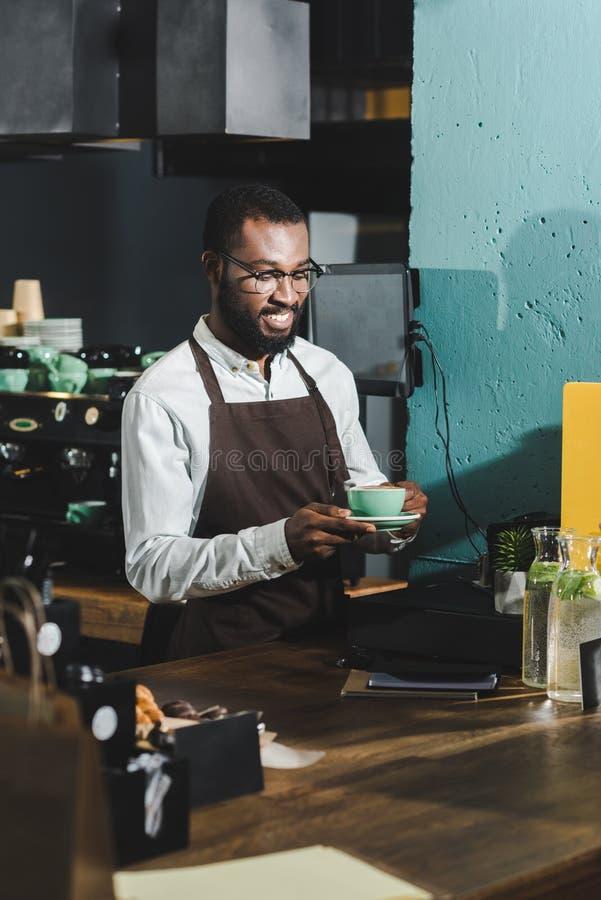 knappe het glimlachen Afrikaanse Amerikaanse barista in oogglazen die kop van koffie houden royalty-vrije stock fotografie