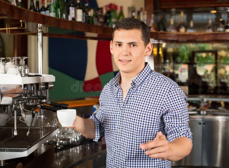 Knappe het glimlachen barista die een kop van koffie houden en FI richten royalty-vrije stock afbeelding