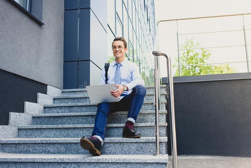 knappe het glimlachen jonge freelancer in oogglazen die op treden zitten en laptop met behulp van royalty-vrije stock foto