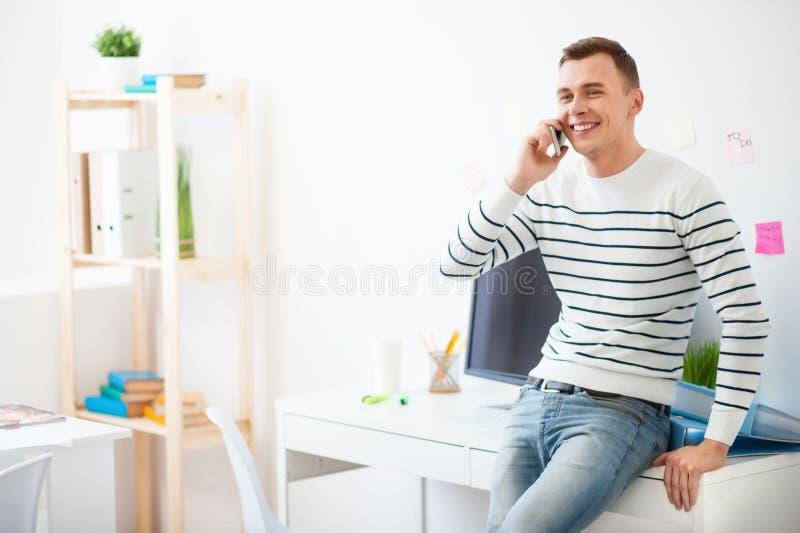 Knappe het glimlachen kerel die op celtelefoon spreken royalty-vrije stock foto