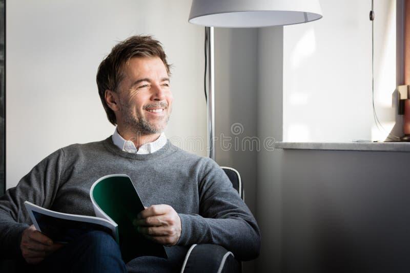 Knappe het glimlachen mensenlezing in een bank die het venster bekijken royalty-vrije stock afbeelding