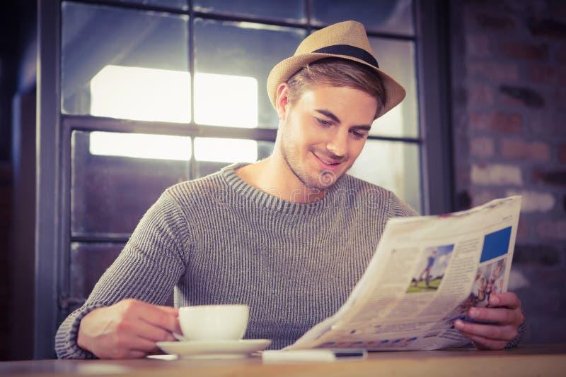 Knappe hipster die koffie hebben en krant lezen stock foto