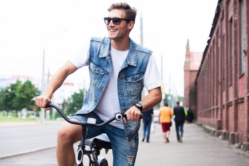 Knappe hipster die stads van rit genieten door fiets stock afbeeldingen