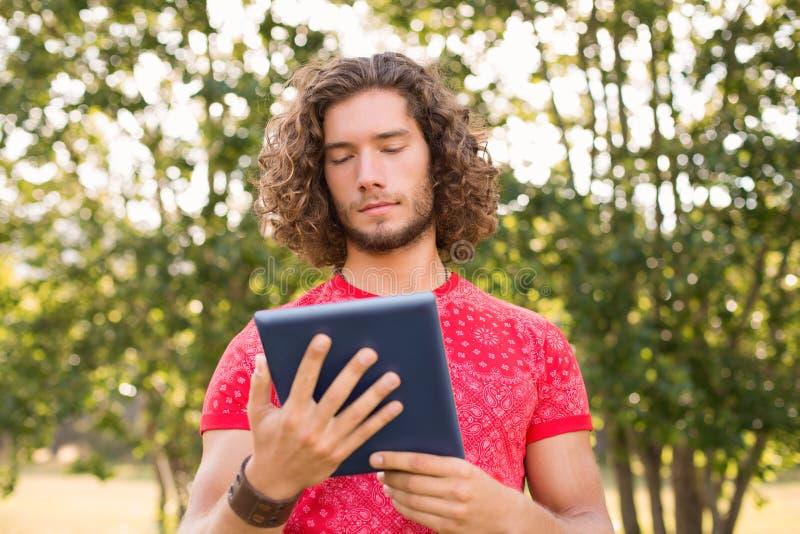 Knappe hipster die tabletpc in het park met behulp van royalty-vrije stock foto