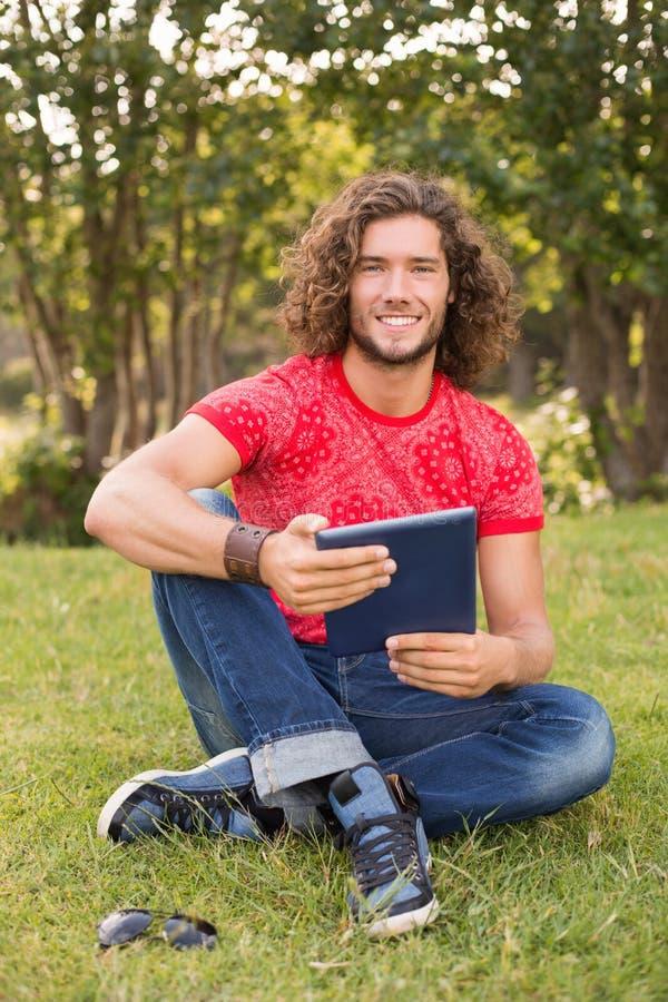 Knappe hipster die tabletpc in het park met behulp van stock afbeeldingen