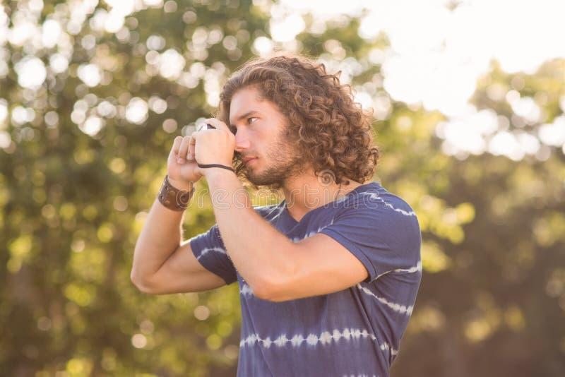 Knappe hipster die uitstekende camera met behulp van royalty-vrije stock fotografie