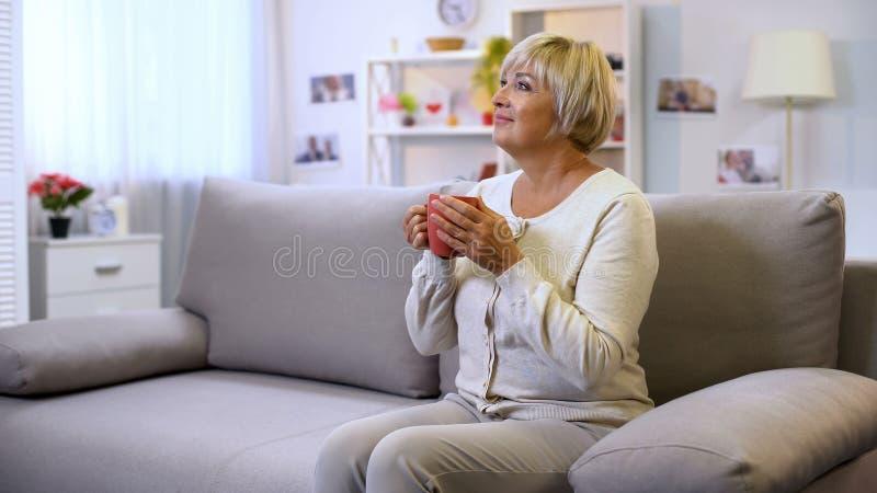 Knappe hogere de theekop van de dameholding, zitting op huisbank, die van weekend genieten royalty-vrije stock foto