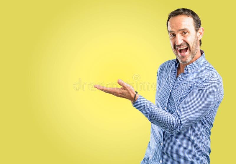 Knappe hogere die mens over gele achtergrond wordt geïsoleerd stock fotografie