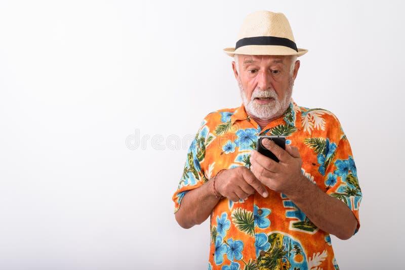 Knappe hogere gebaarde toeristenmens die geschokt terwijl het gebruiken van telefoon kijken royalty-vrije stock fotografie