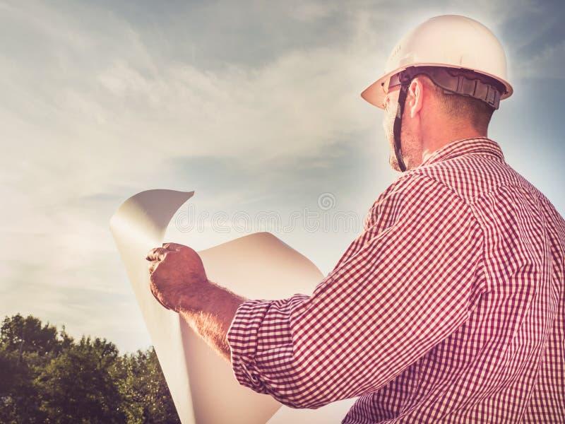 Knappe ingenieur in een witte bouwvakker stock foto's