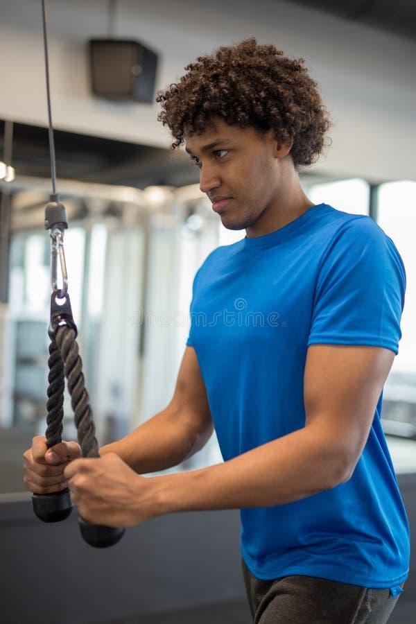 Knappe jonge Afrikaanse Amerikaanse mens die bij de gymnastiek uitwerken stock foto's