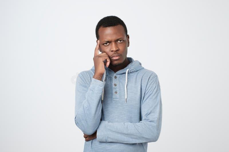 Knappe jonge Afrikaanse Amerikaanse mens die omhoog met nadenkende en sceptische uitdrukking kijken royalty-vrije stock afbeelding