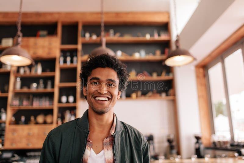 Knappe jonge Afrikaanse kerel die zich in een koffie winkel en het glimlachen bevinden stock fotografie