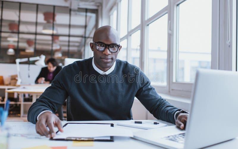 Knappe jonge Afrikaanse mens bij zijn bureau met laptop stock foto's