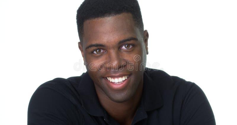 Knappe jonge Afrikaanse mens die bij camera glimlacht stock foto's
