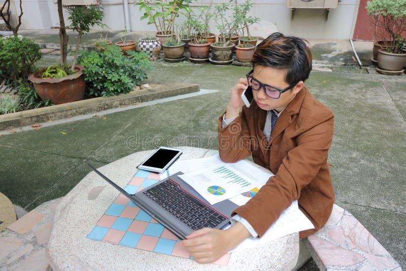Knappe jonge bedrijfsmens die op de telefoon met klant spreken stock foto