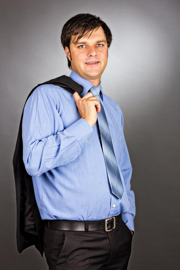 Knappe jonge bedrijfsmens die zijn kostuumjasje op zijn shoul houden stock foto's