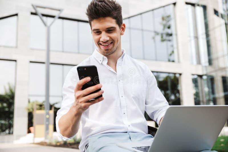 Knappe jonge bedrijfsmensenzitting die in openlucht laptop computer en mobiele telefoon met behulp van royalty-vrije stock afbeelding