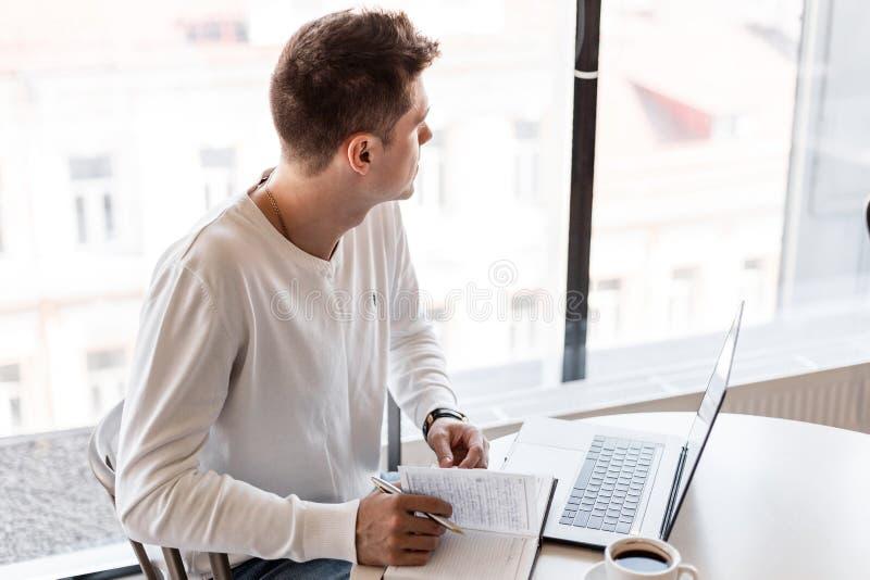 Knappe jonge blogger met laptop in een wit overhemd zit bij een lijst in het bureau en neemt nota's in een notitieboekje royalty-vrije stock foto