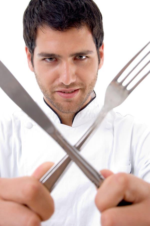 Knappe jonge chef-kok met bestek royalty-vrije stock afbeeldingen