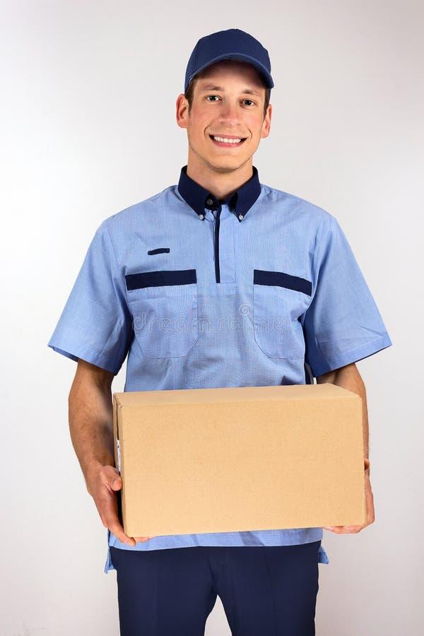 Knappe jonge dragende het kartondoos van de leveringsmens stock fotografie