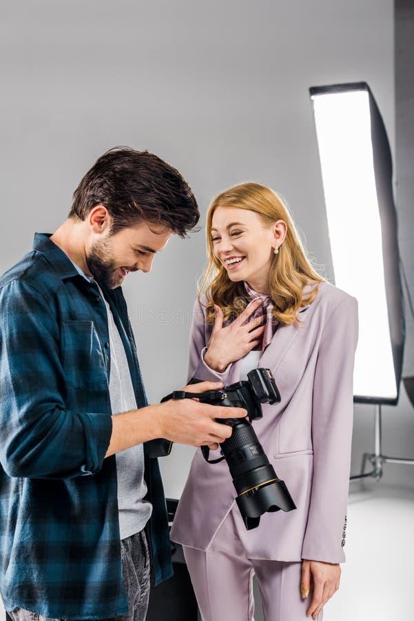 knappe jonge fotograaf en het glimlachen vrouwelijke model gebruikende fotocamera en het lachen stock afbeeldingen