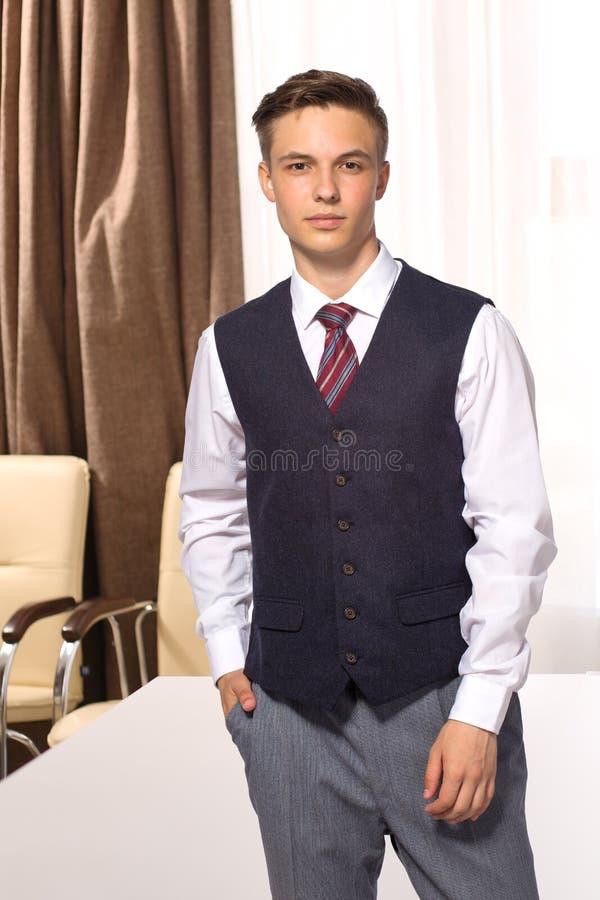 Knappe jonge glimlachende zakenman in de bestuurskamer stock foto's