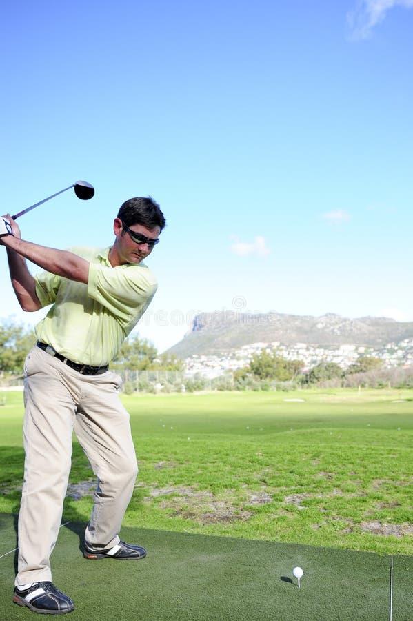 Knappe jonge golfspeler in actie stock foto's