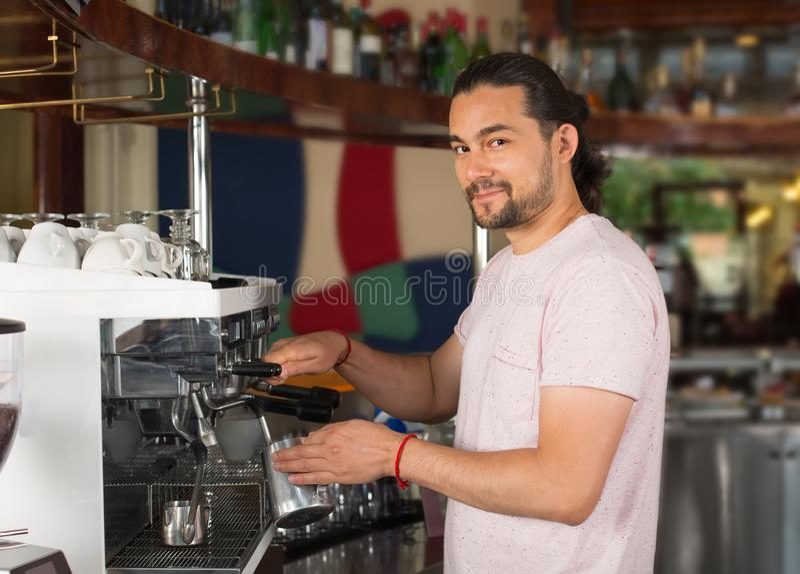 Knappe jonge het glimlachen mannelijke barista die koffiedrank het gebruiken voorbereiden royalty-vrije stock foto's